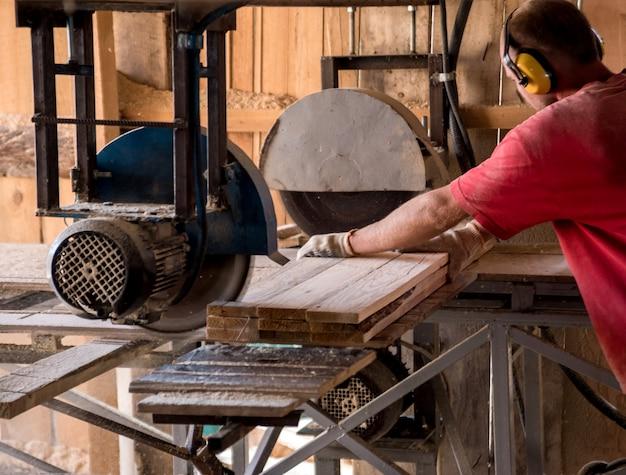 Segheria moderna. un falegname lavora alla lavorazione del legno della macchina utensile.