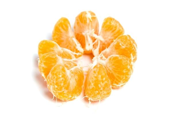 Segmenti pelati succosi di mandarino isolati su priorità bassa bianca