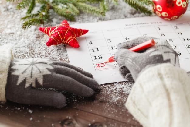 Segna il calendario delle date per natale, il 25 dicembre, con decorazioni festive