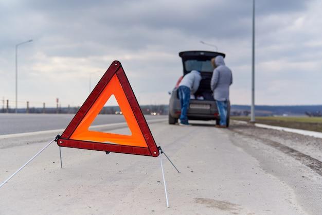 Segnale di avvertimento sulla strada su un offuscata di persone vicino alla macchina.