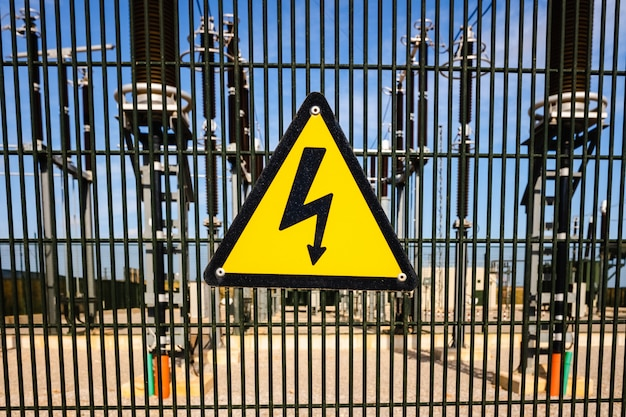 Segnale di pericolo per elettrocuzione di fronte a un'installazione di trasformatori elettrici.