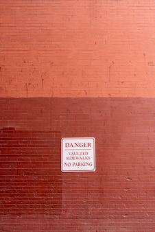 Segnale di pericolo sulla vista frontale del muro di mattoni