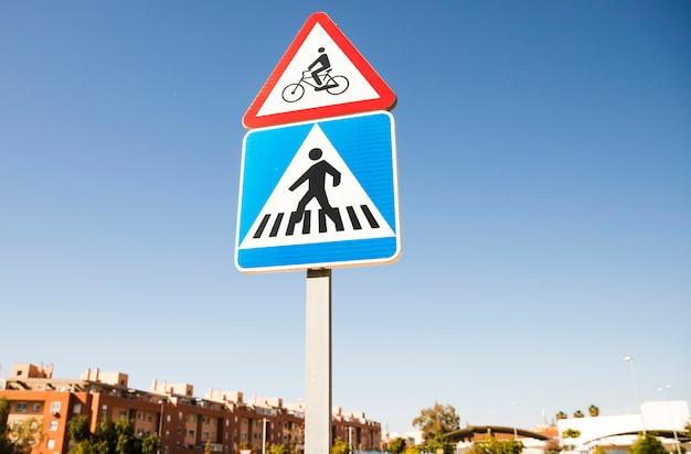 Segnale di pericolo triangolare della bicicletta sopra il segnale stradale quadrato del passaggio pedonale dentro la città