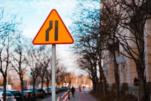 Segnale stradale a triangolo. la strada si restringe sul lato sinistro
