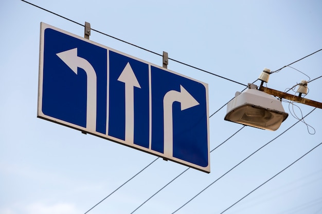 Segnale stradale alto sopra la strada con tre frecce bianche su sfondo blu che mostra la direzione.