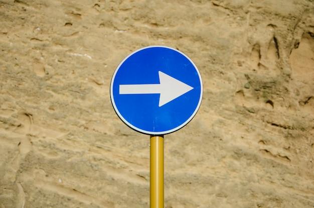 Segnale stradale blu con la freccia sulla parete antica stagionata