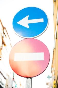 Segnale stradale di fermata rossa e segno direzionale sulla strada