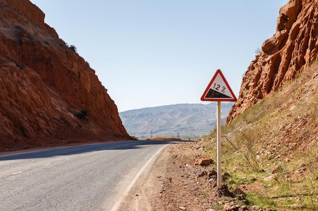 Segnale stradale in discesa con la percentuale su una strada della montagna, segnale stradale d'avvertimento kirghizistan