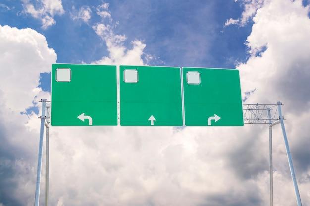 Segnale stradale verde in bianco di traffico sul fondo delle nuvole e del cielo