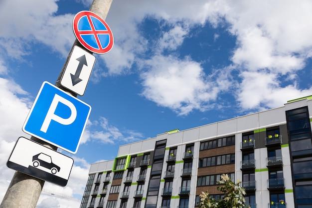 Segnali stradali nessuna attesa e metodo di parcheggio del veicolo contro il cielo e il condominio