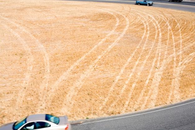 Segni di pneumatici su erba secca