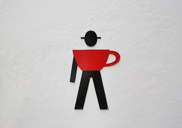 Segni maschili della toilette sulla parete del cemento bianco del caffè.