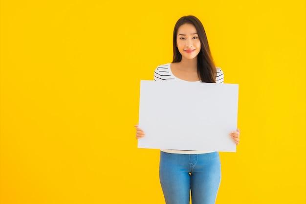Segno bianco vuoto del tabellone per le affissioni di bella giovane manifestazione asiatica della donna del ritratto