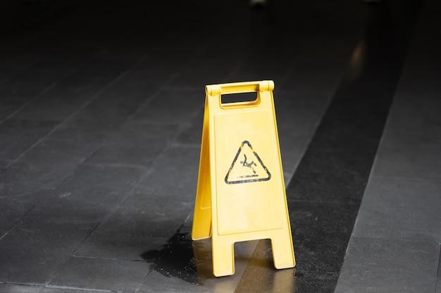 Segno che mostra avvertimento del pavimento bagnato di cautela in aeroporto.