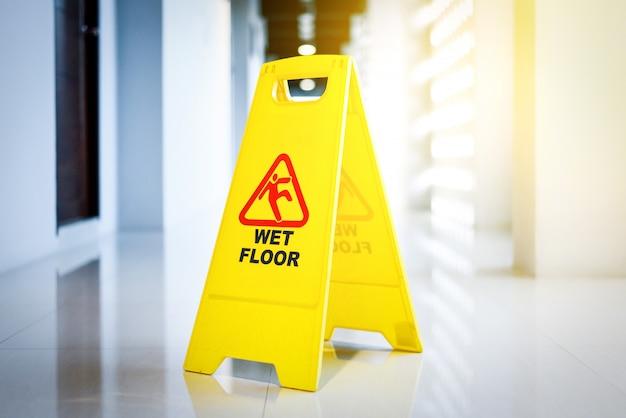 Segno che mostra avvertimento del pavimento bagnato sul pavimento bagnato
