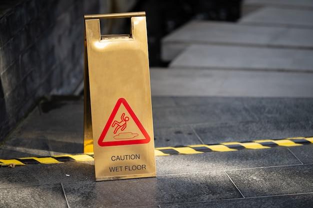 Segno che mostra l'avvertimento del pavimento bagnato di attenzione vicino all'area bagnata