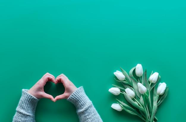 Segno del cuore di manifestazione della mano della donna, mazzo di tulipani bianchi sul libro verde della menta. vista piana a molla, vista dall'alto con copia-spazio.