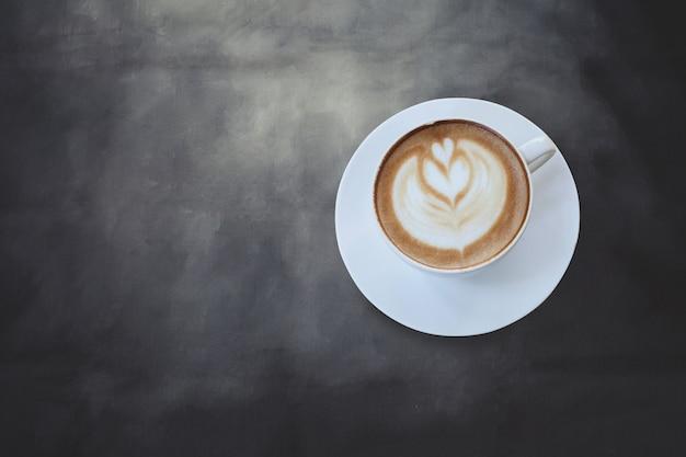 Segno del cuore sul caffè di arte del latte sul fondo nero di colore.