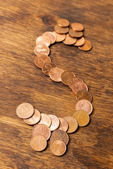 Segno del dollaro fatto dalle monete su fondo di legno
