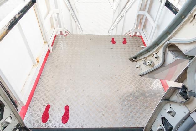 Segno del piede sul corridoio dell'aeroplano, protocollo di allontanamento sociale sull'aviazione