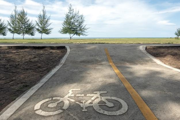 Segno del vicolo della bici / segnale stradale dietro la spiaggia con erba verde e cielo blu