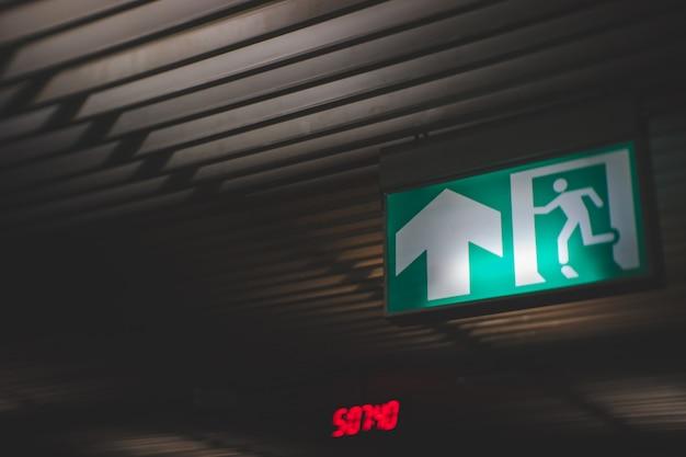 Segno dell'uscita di sicurezza su fuoco nell'edificio.