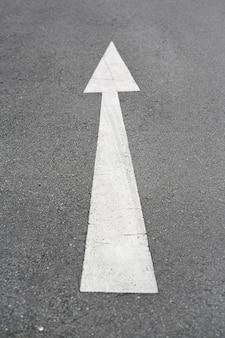 Segno della freccia che segna su una strada