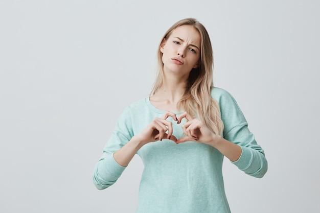 Segno di amore di mostra femminile biondo con le sue mani a forma di cuore. la bella donna europea vestita con indifferenza sente l'amore. concetto di romanticismo e relazioni umane.