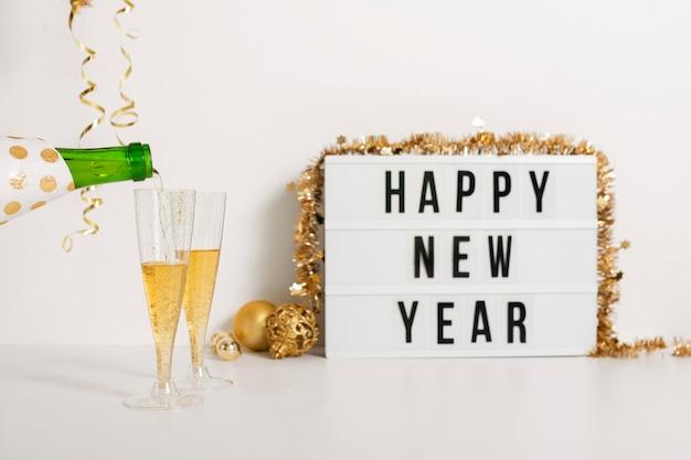 Segno di felice anno nuovo con bicchieri di champagne