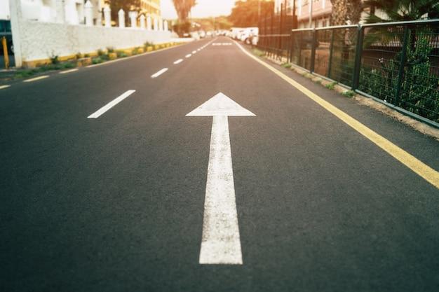 Segno di freccia bianca sulla strada vuota.
