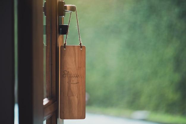 Segno di legno con il sorriso del testo appeso di fronte alla stanza