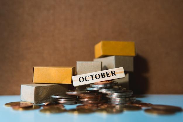 Segno di ottobre in legno con un mucchio di monete e scatole di cartone