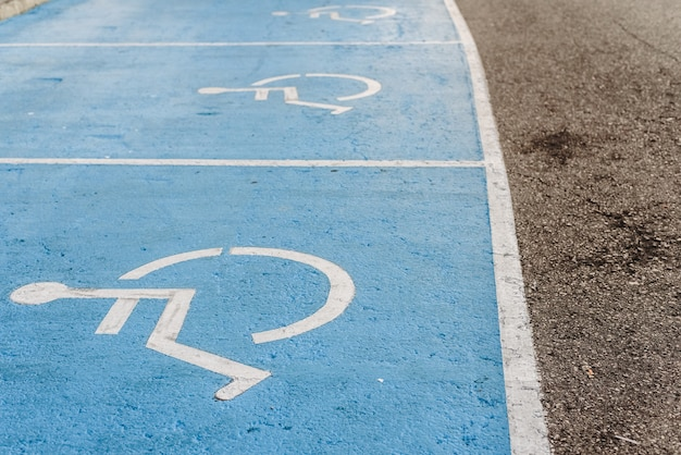 Segno di parcheggio per disabili dipinto sul pavimento, esempio di integrazione di persone con minore mobilità.