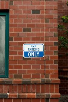 Segno di parcheggio sulla vista frontale del muro di mattoni