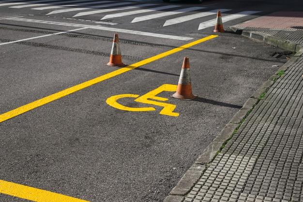 Segno di sedia a rotelle appena dipinto sulla strada per contrassegnare un parcheggio per disabili.