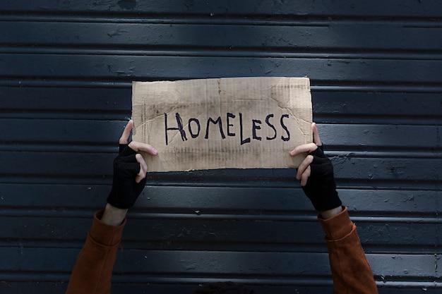 Segno di senzatetto tenuto da mani di un mendicante