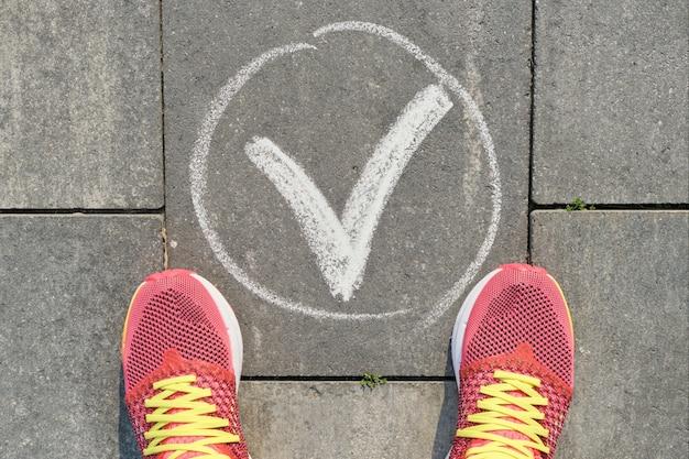 Segno di spunta ok segno sul marciapiede grigio con gambe di donna