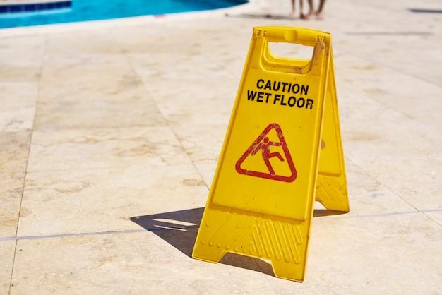 Segno giallo di avvertenza del pavimento bagnato nel giorno di estate