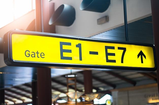 Segno giallo illuminato all'aeroporto con il numero di porta per i voli in partenza