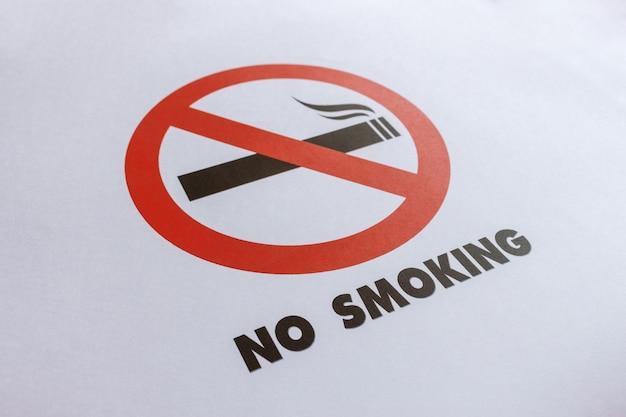 Segno non fumatori del primo piano su libro bianco