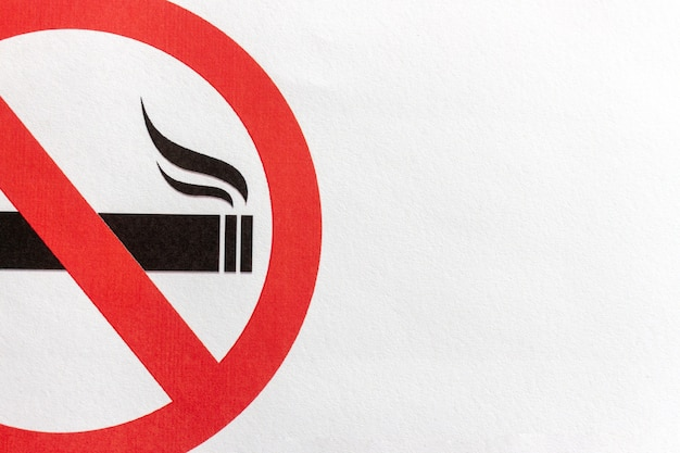 Segno non fumatori del primo piano sul fondo del libro bianco