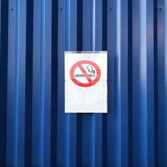 Segno non fumatori sulla parete blu