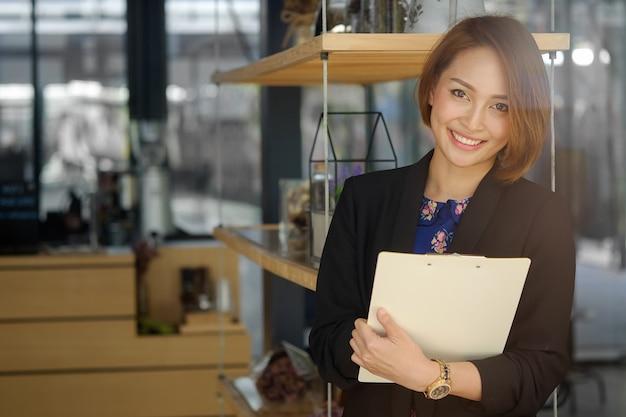 Segretaria donna in possesso di un file di documenti e sorridere sul viso.
