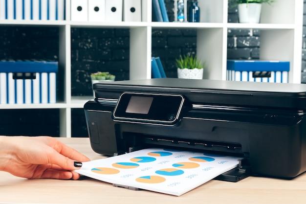 Segretaria femminile che fa le fotocopie sulla macchina di xerox in ufficio