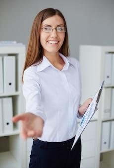 Segretaria sorridente con gli occhiali e camicia bianca
