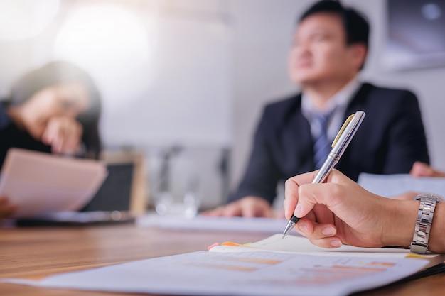 Segretario donna prendendo appunti per il suo capo durante la riunione d'affari.