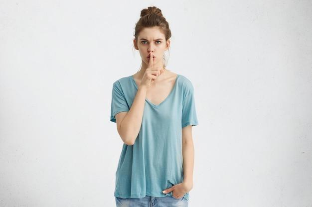 Segretezza, privacy e riservatezza. attraente giovane donna con uno sguardo serio e rigoroso tenendo il dito indice sulle labbra, dicendo shh, chiedendo silenzio o chiedendo di mantenere segrete le informazioni private