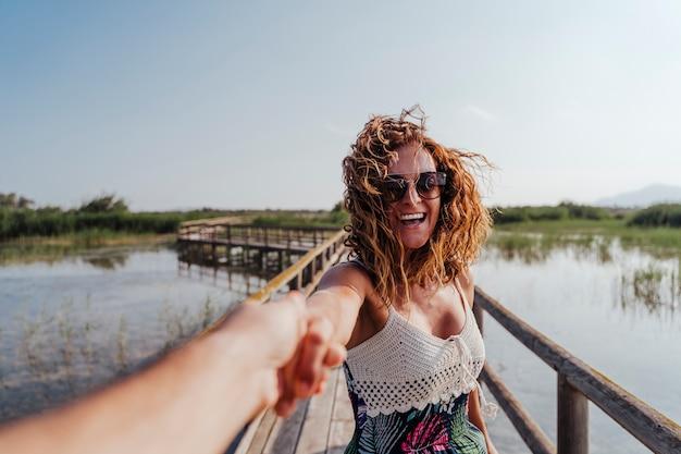 Seguimi donna in un parco naturale tenendo la mano del fidanzato