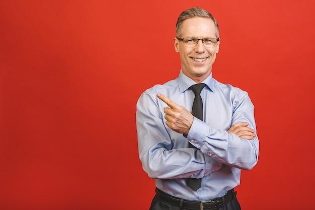 Seguimi! guarda qui! chiuda sul ritratto dell'uomo d'affari invecchiato allegro con esperienza qualificato soddisfatto soddisfatto allegro che indica sul posto in bianco vuoto isolato sulla parete rossa.