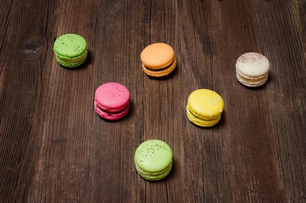 Sei macarons multicolori su un tavolo di legno marrone. vista dall'alto